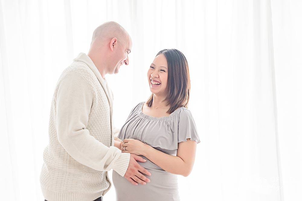 couple shares a laugh in natural light studio