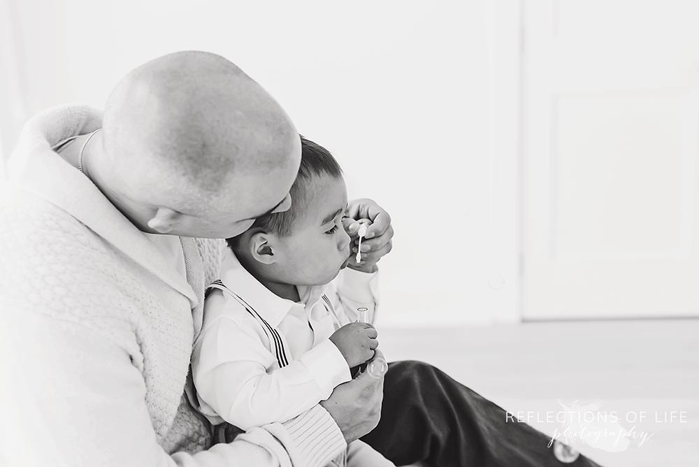 dad guides his son while he tries to blow a bubble in black and white
