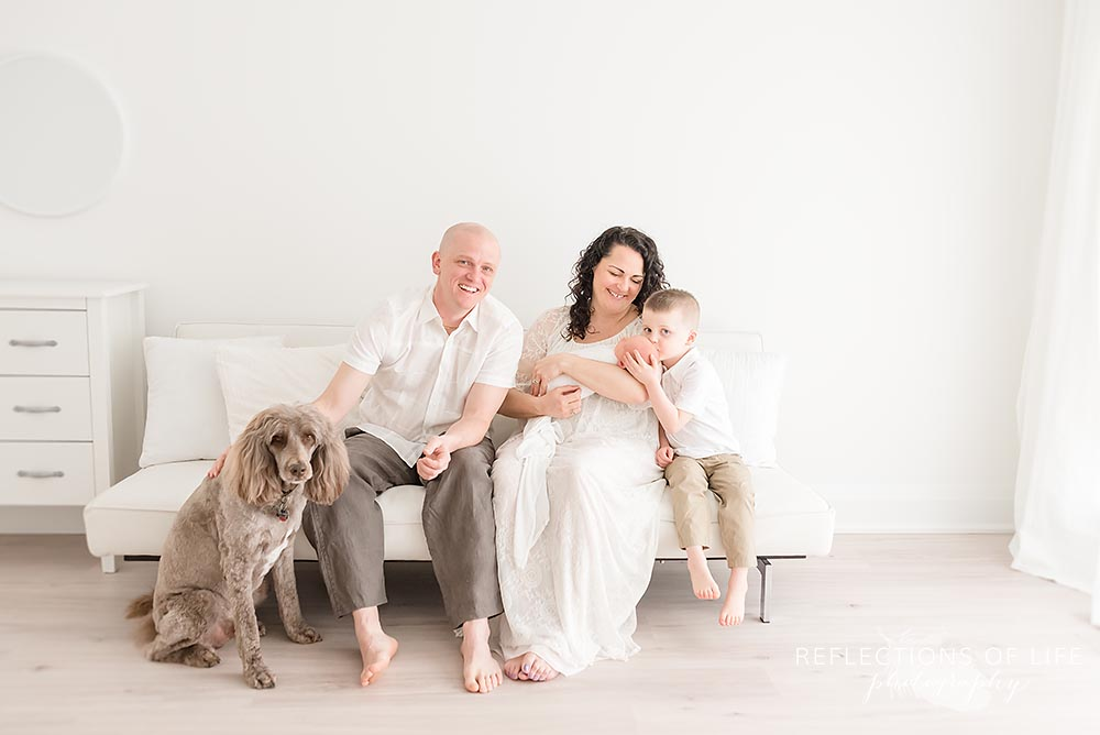 family of four sit on a couch as dad pets their dog in natural light studio