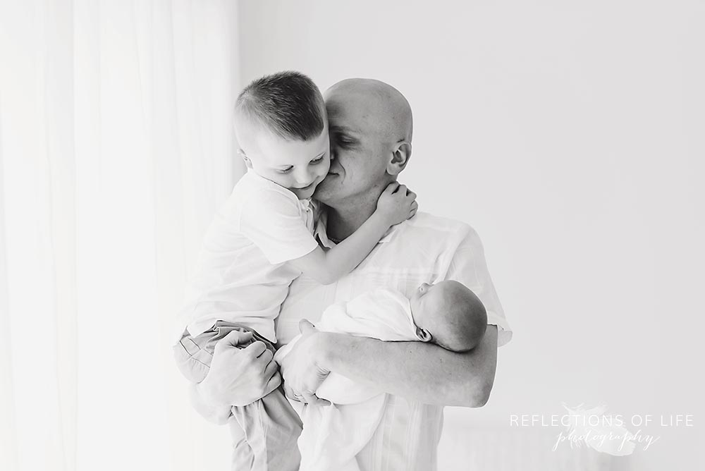 dad holds his two babies as he hugs them in black and white