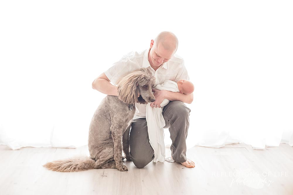 dad and his baby crouch on the ground to pet his dog in natural light studio