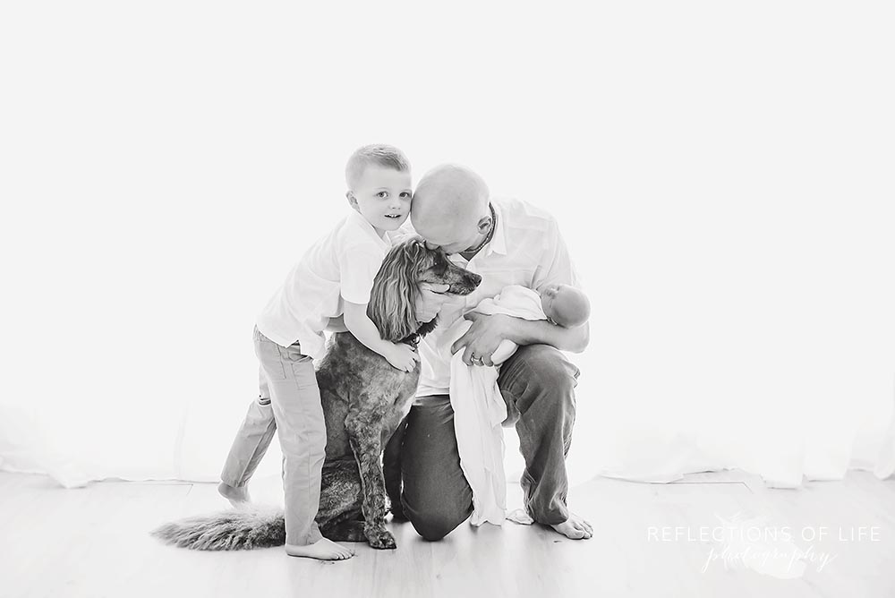 son joins his father and baby as they all snuggle their dog in black and white