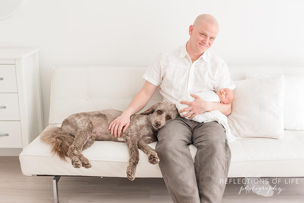 dad and baby sit on the couch with their family dog laying on his lap