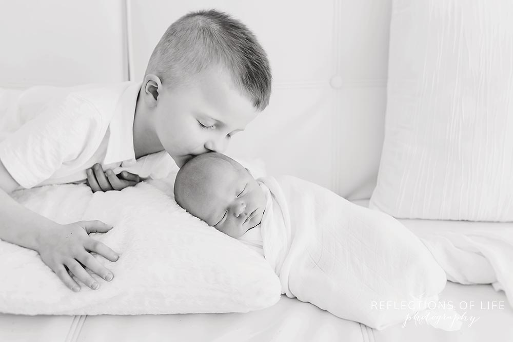 brother kisses his new siblings kid in black and white