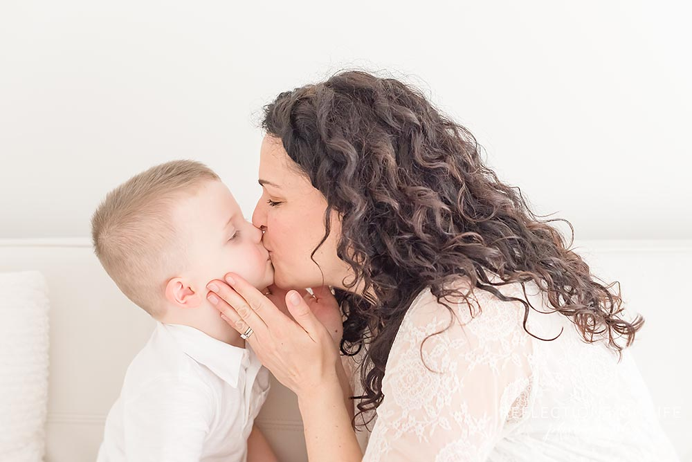 mama kisses her son in natural light studio