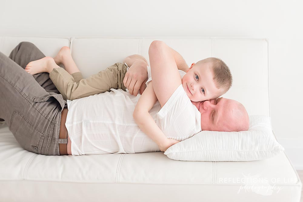 father snuggles his son on couch in natural light studio