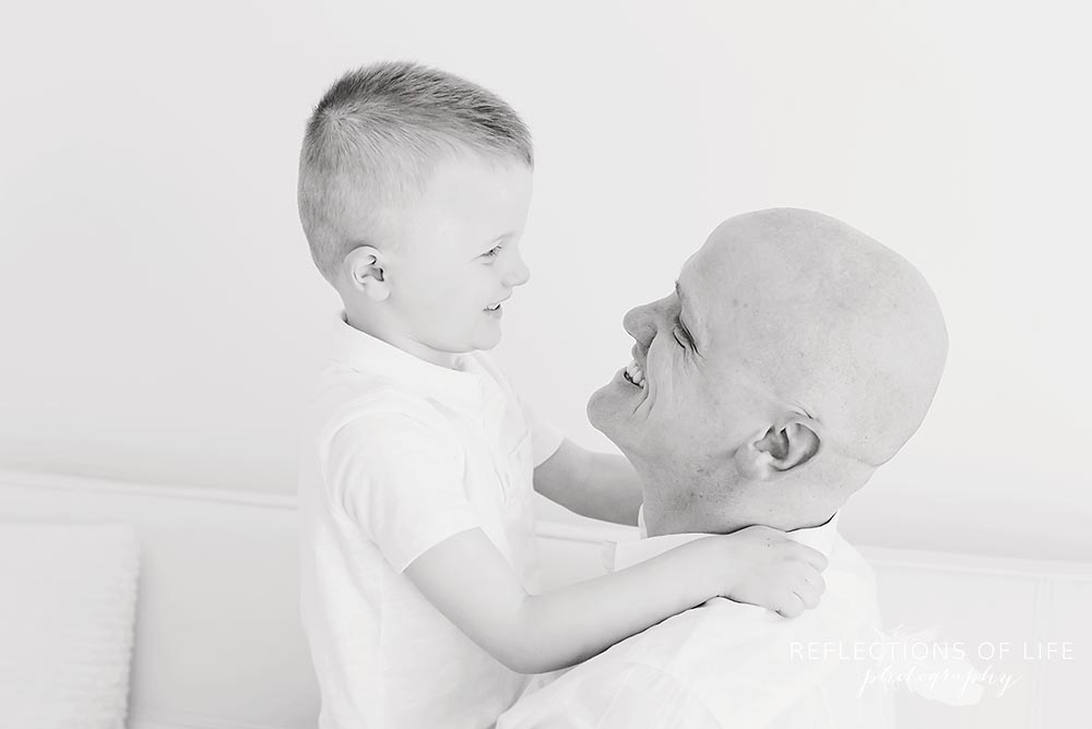 father and son smile at each other in black and white