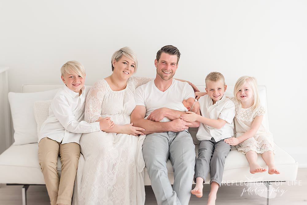 family of six sits on a couch holding their new daughter in natural light studio