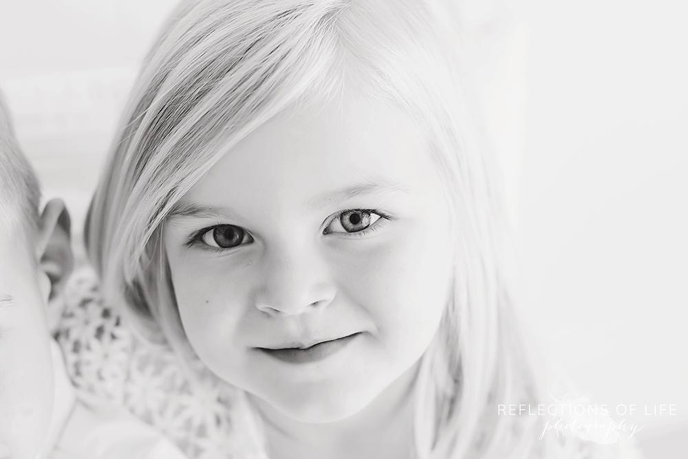 little girl smirks at the camera in natural light studio black and white