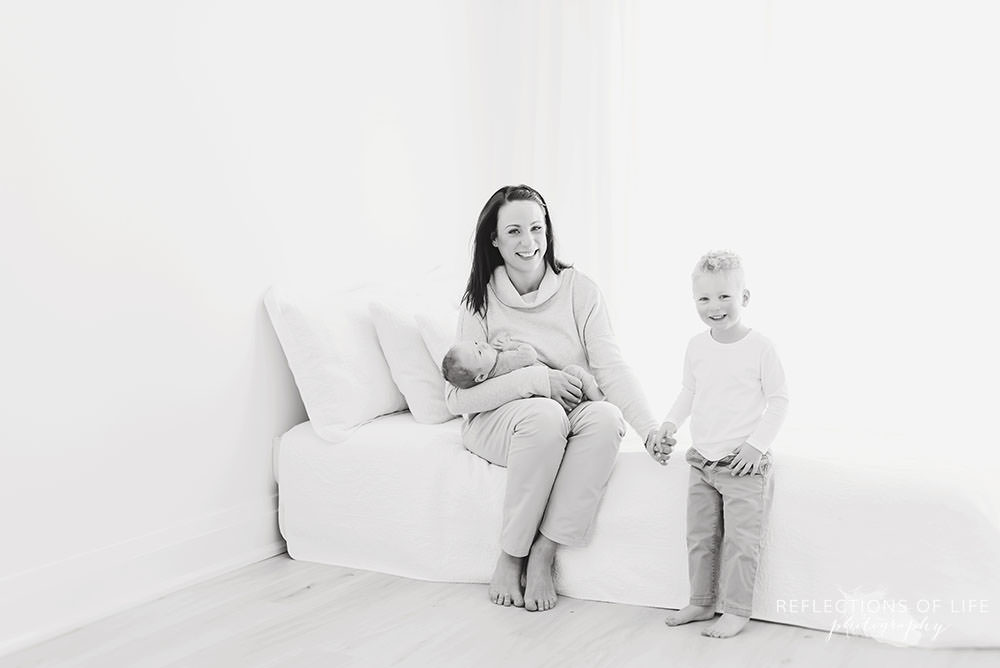 mama with her two sons sit on a bed and smile at the camera in black and white