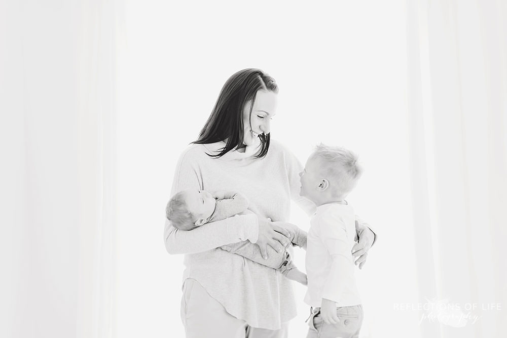 mama smiles at her oldest son as she holds her baby in black and white