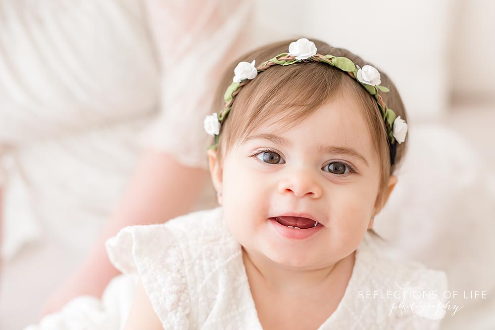 baby giggles at the camera in natural light studio
