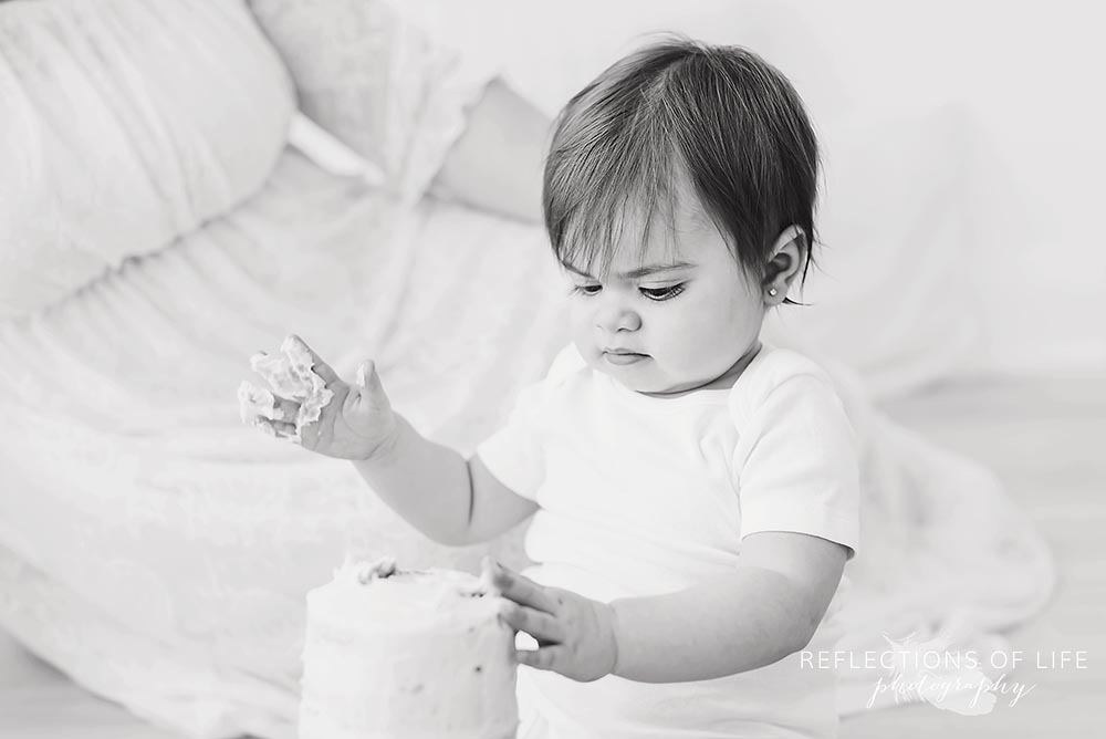 little girl gets messy with her cake in black and white