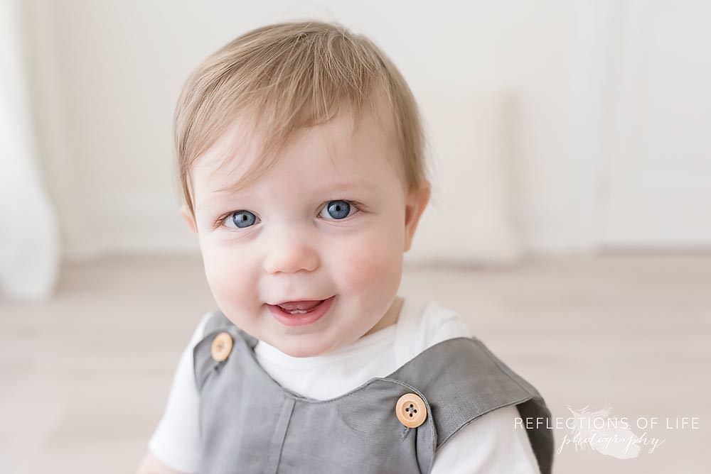 little boy smiles at the camera in natural light studio