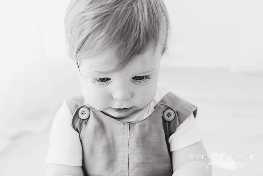 little boy looks at the ground in black and white