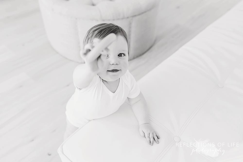 little boy shows the camera his toy in black and white