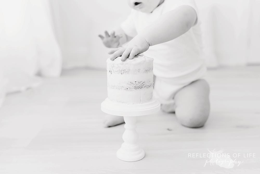 close up of baby's hand on a cake in black and white