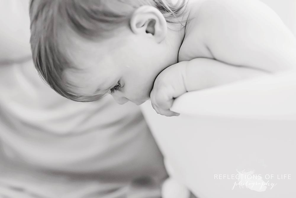 baby looks over the side of the tub in black and white