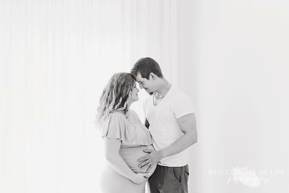 couple looks at each other smiling as he touches her belly in black and white