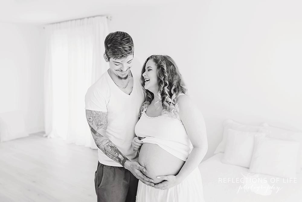 couple laughs together in natural light studio as dad holds her belly in black and white