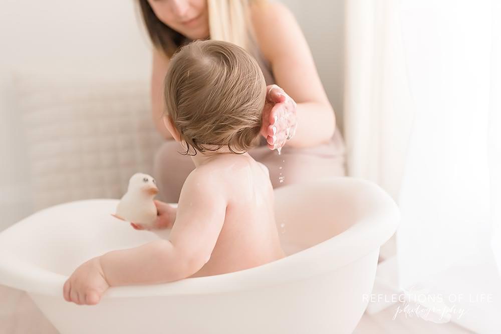 Mama baths baby in natural light studio Niagara Ontario.jpg