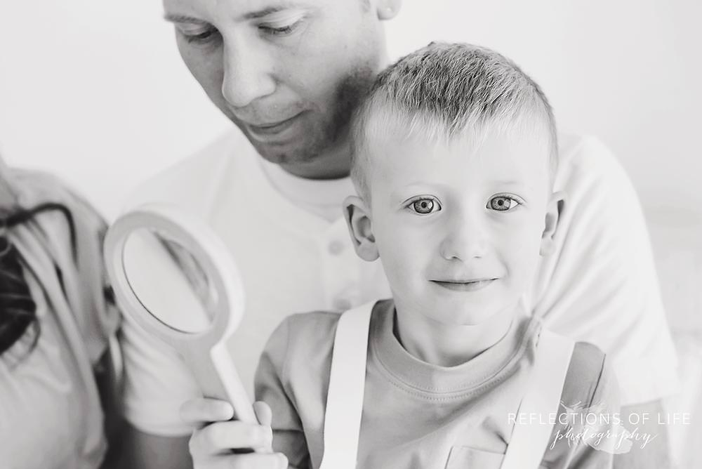 Little boy smiles at the camera with a magnifying glass in his hand niagara child photographer