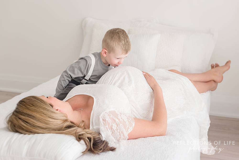 Pregnant mom with her son playing cars on her belly Niagara Maternity Photos