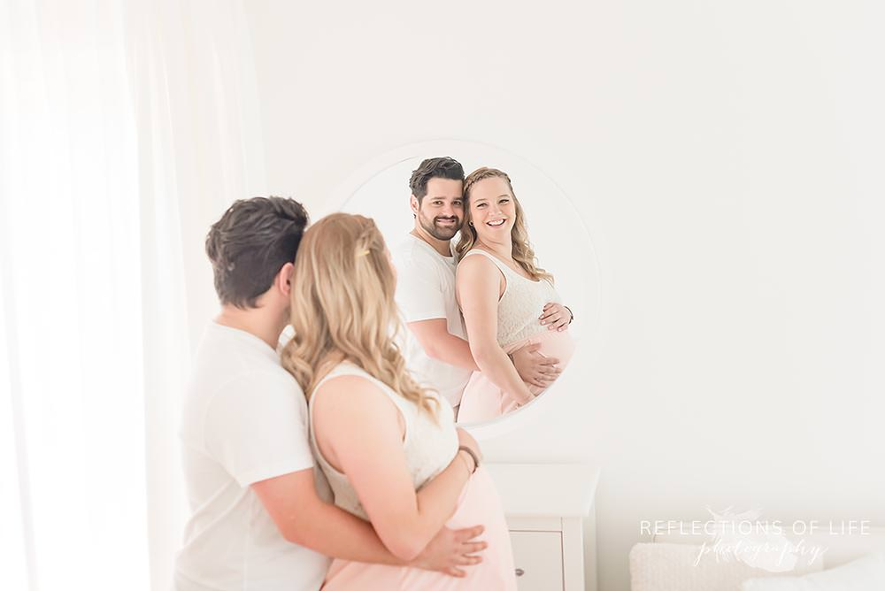 beautiful pregnant couple reflected in mirror