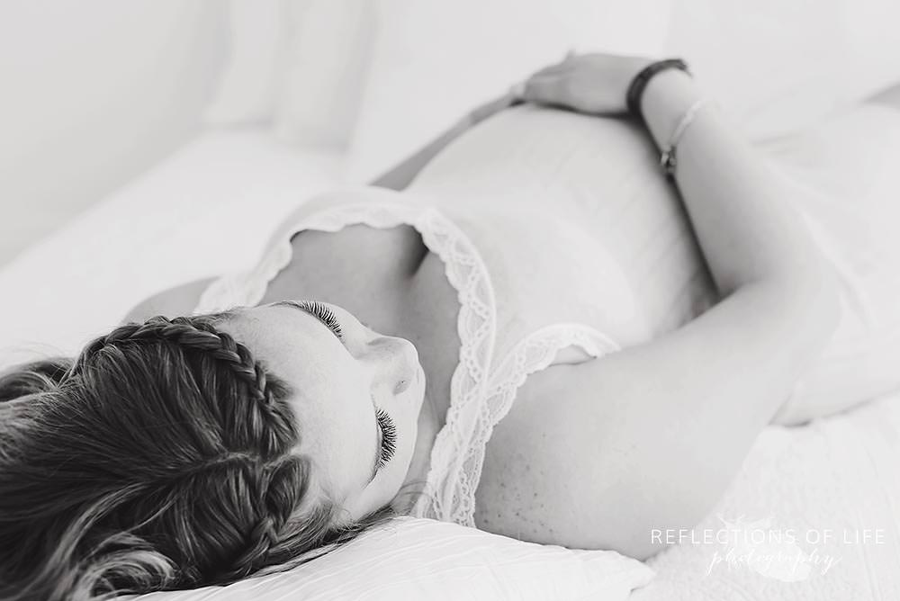 Beautiful pregnant mama in black and white laying on bed