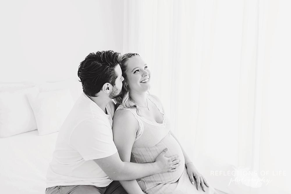 pregnant couple laughing in black and white