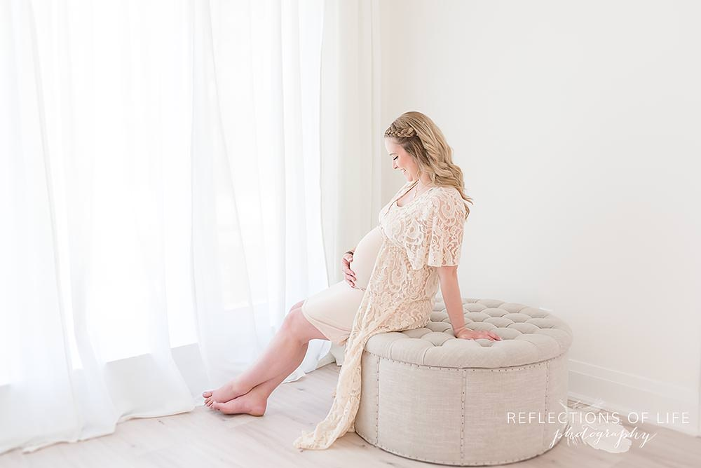 Mama in cream lace dress with hands on her belly near a large window