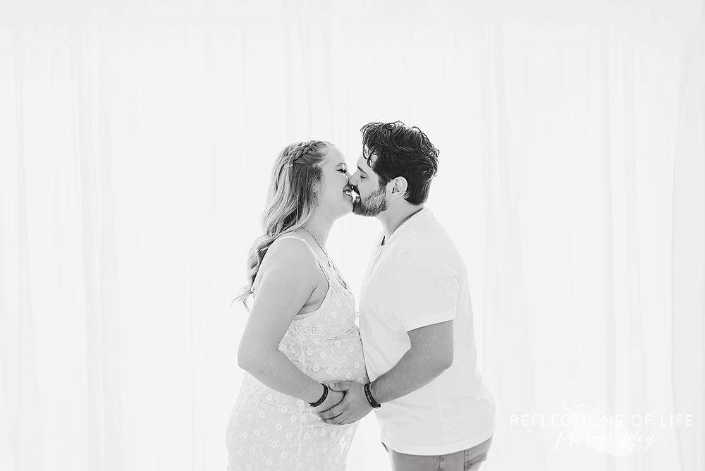 Pregnant couple about to kiss in natural light studio in Grimsby