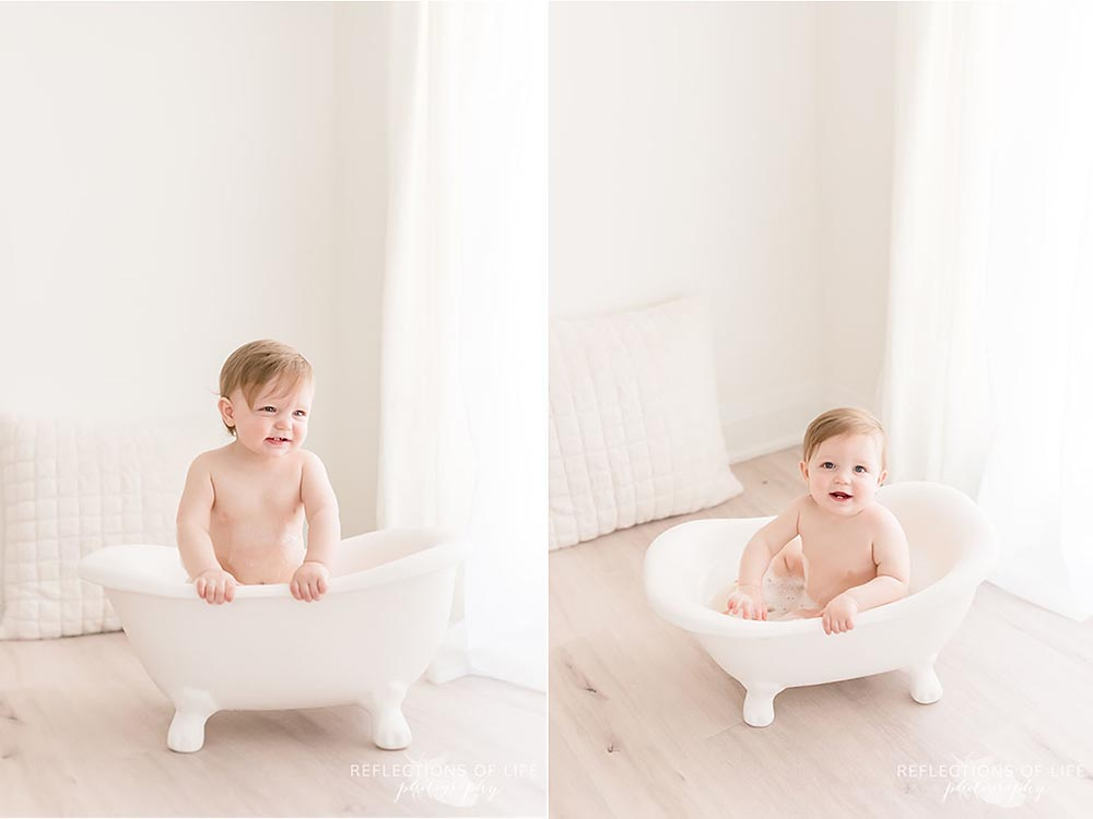 baby boy peeks over the side of his baby sized bathtub