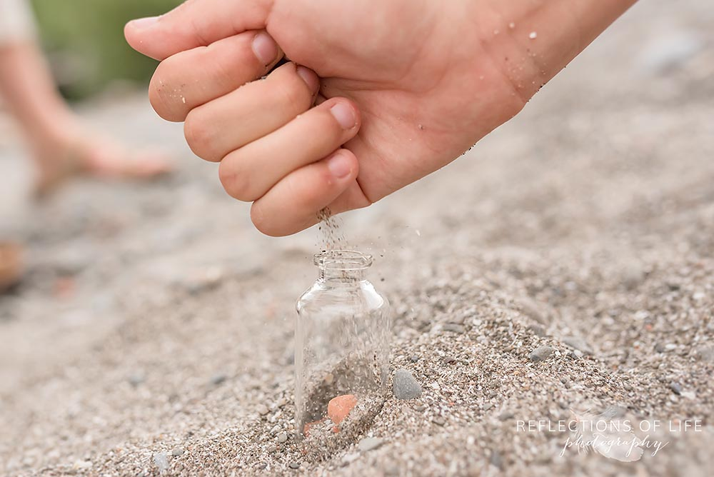 Dropping sand into a small glass jar during a family session in Grimsby Ontario
