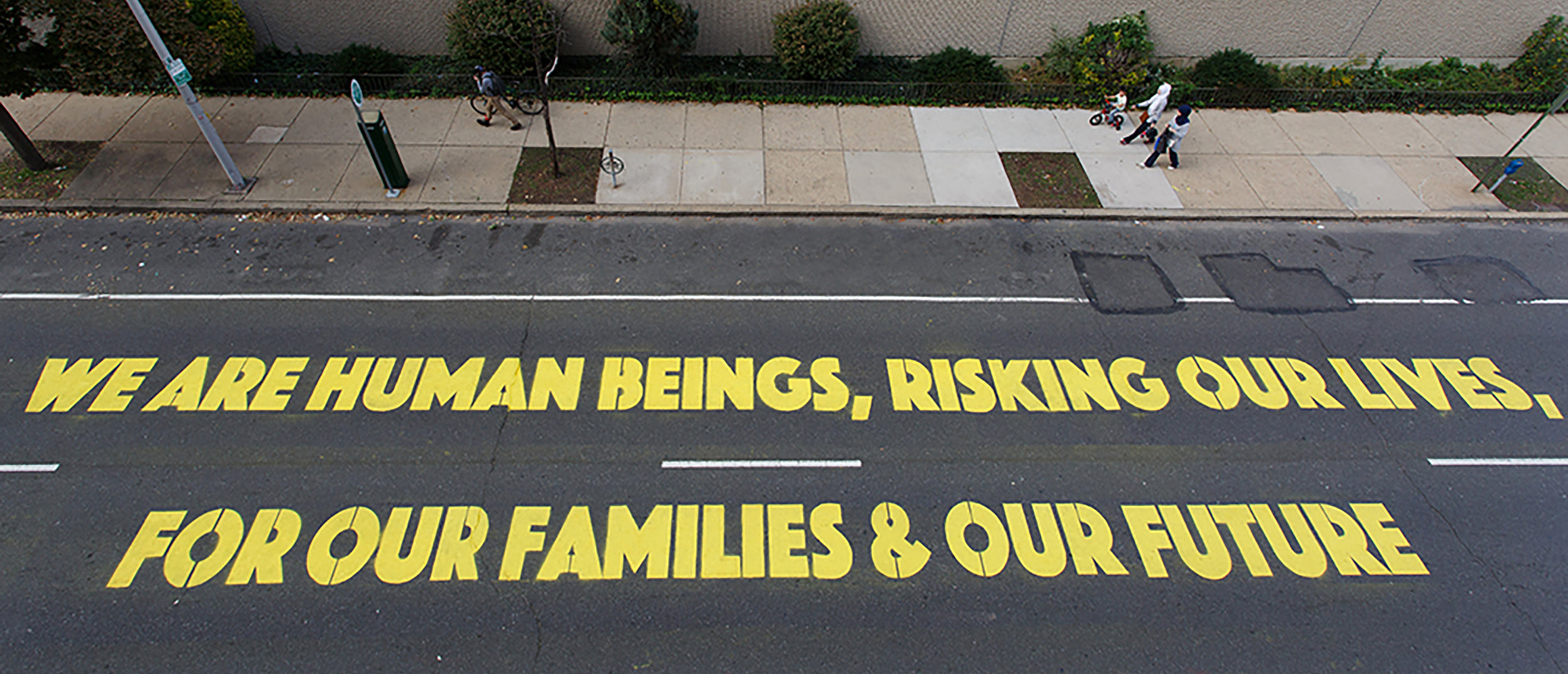 "Photo Credit: Steve Weinik. ""We Are Human Beings"" installed in front of the ICE building in Philadelphia."