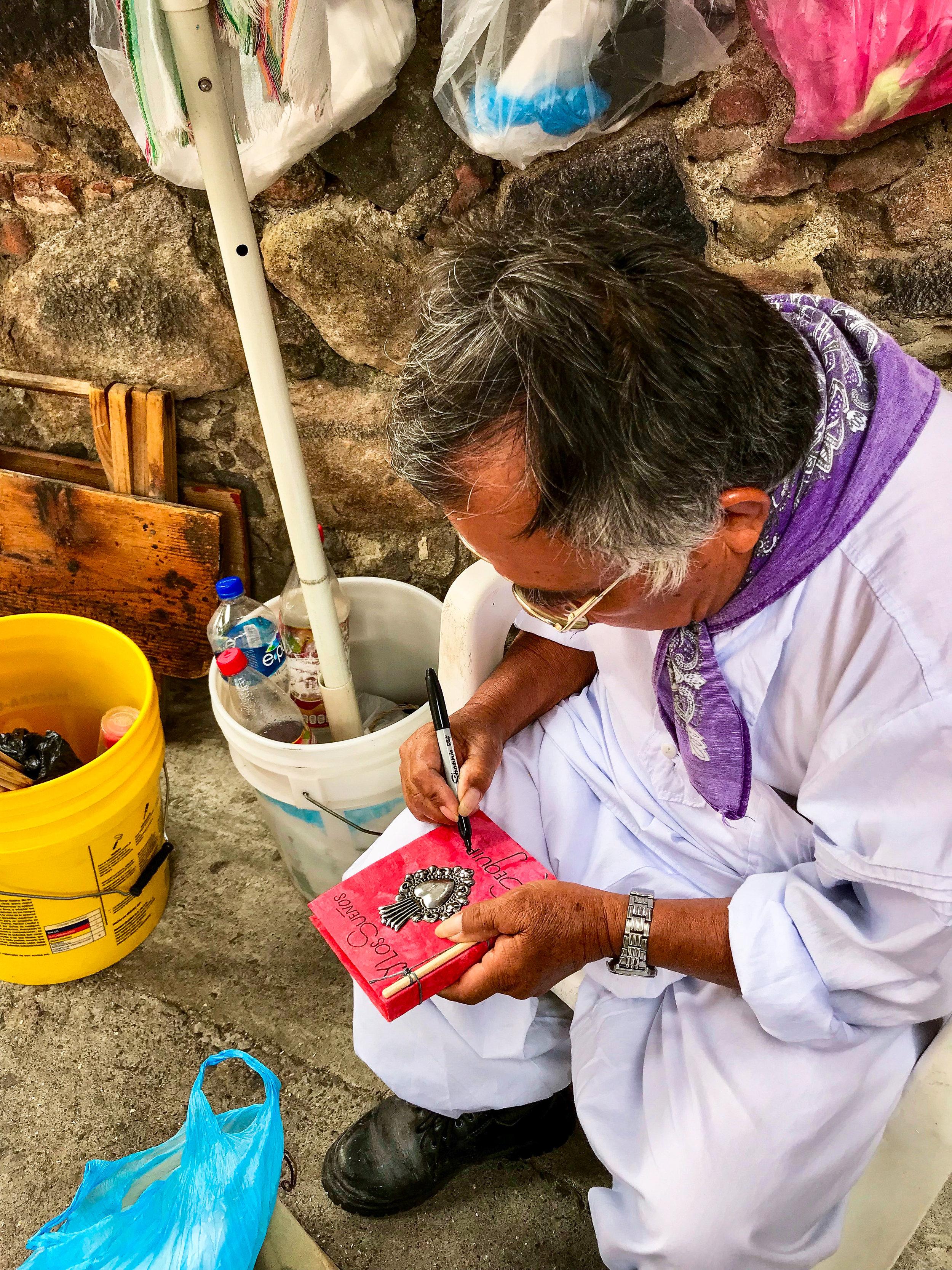 An Artisan making me a notepad in Door in San Miguel de Allende, Guanajuato, Mexico.