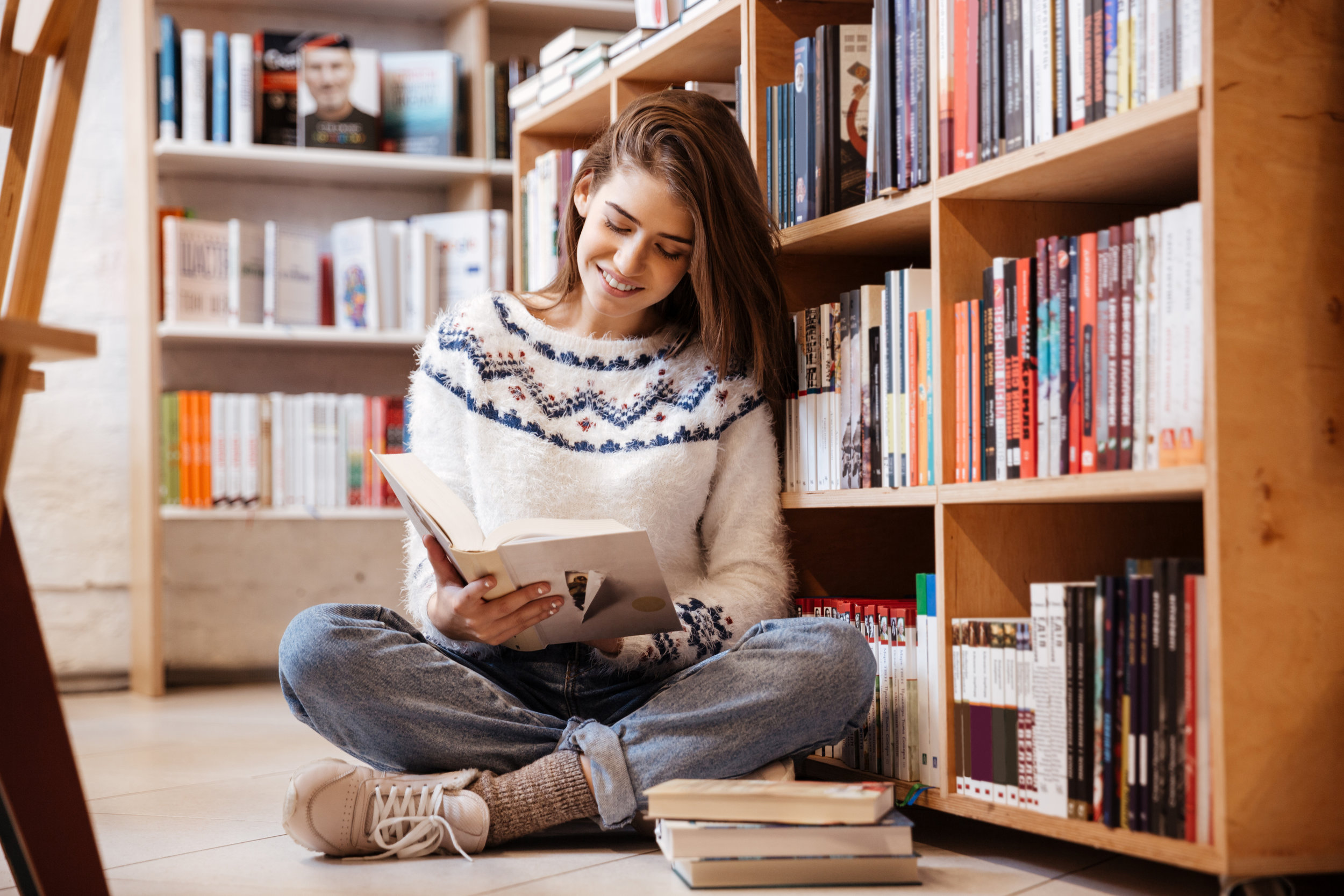 graphicstock-pretty-young-female-student-reading-book-on-library-floor-at-the-university_HUcrHDmdhg.jpg