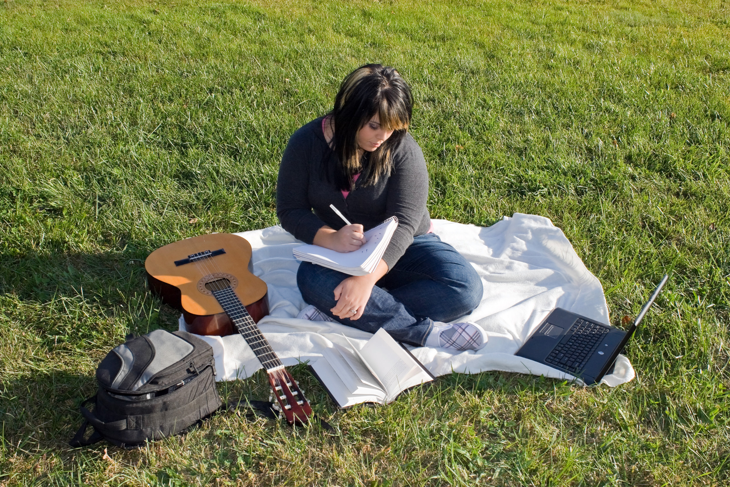 a-young-female-singer-or-song-writer-with-her-guitar-and-computer-outdoors-in-the-grass_rK8gpFFABj.jpg