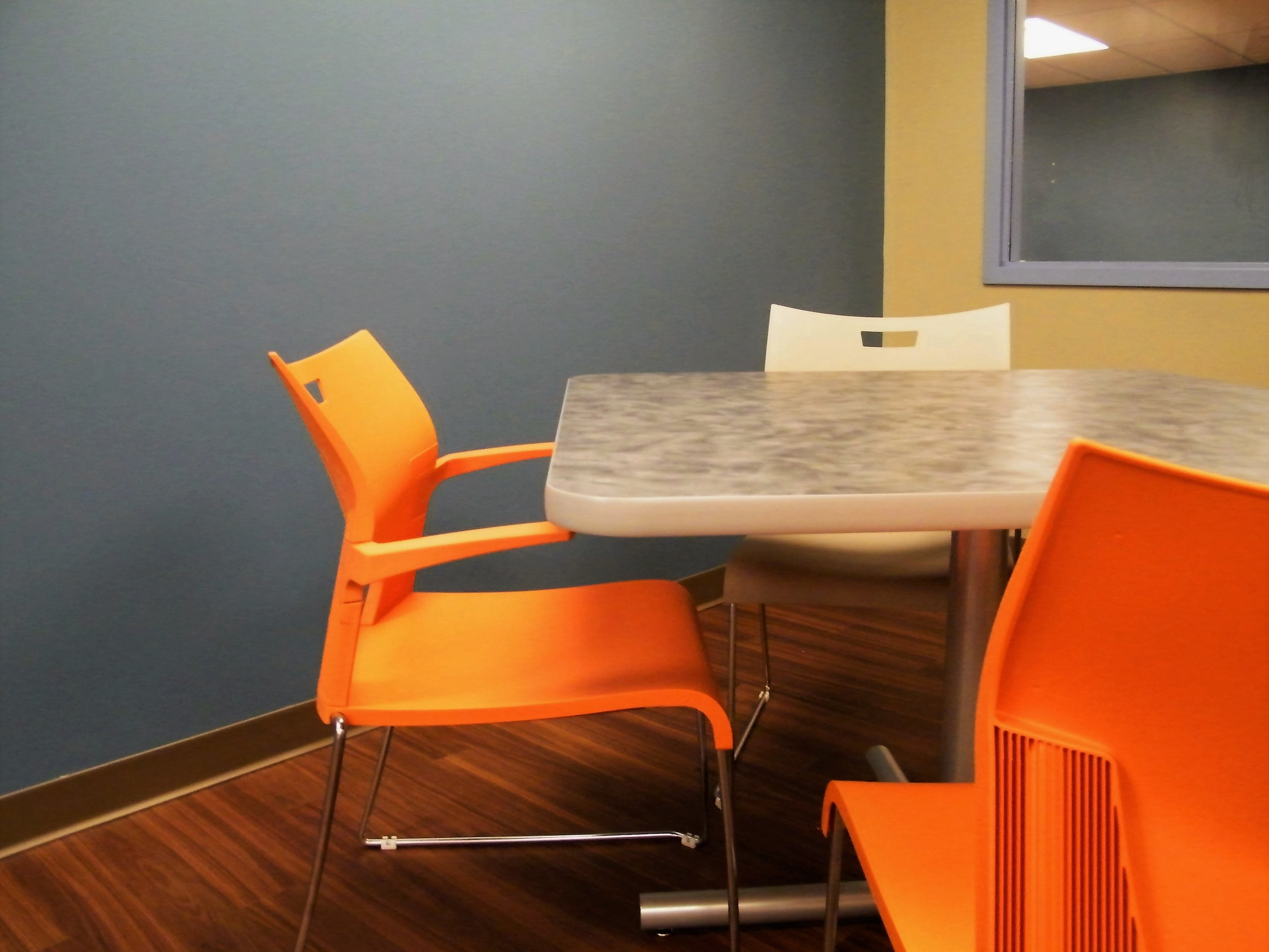PVC Table with Laminate Top on Cross Base with Duet Chairs with Arms and Without Arms in Orange and Grey