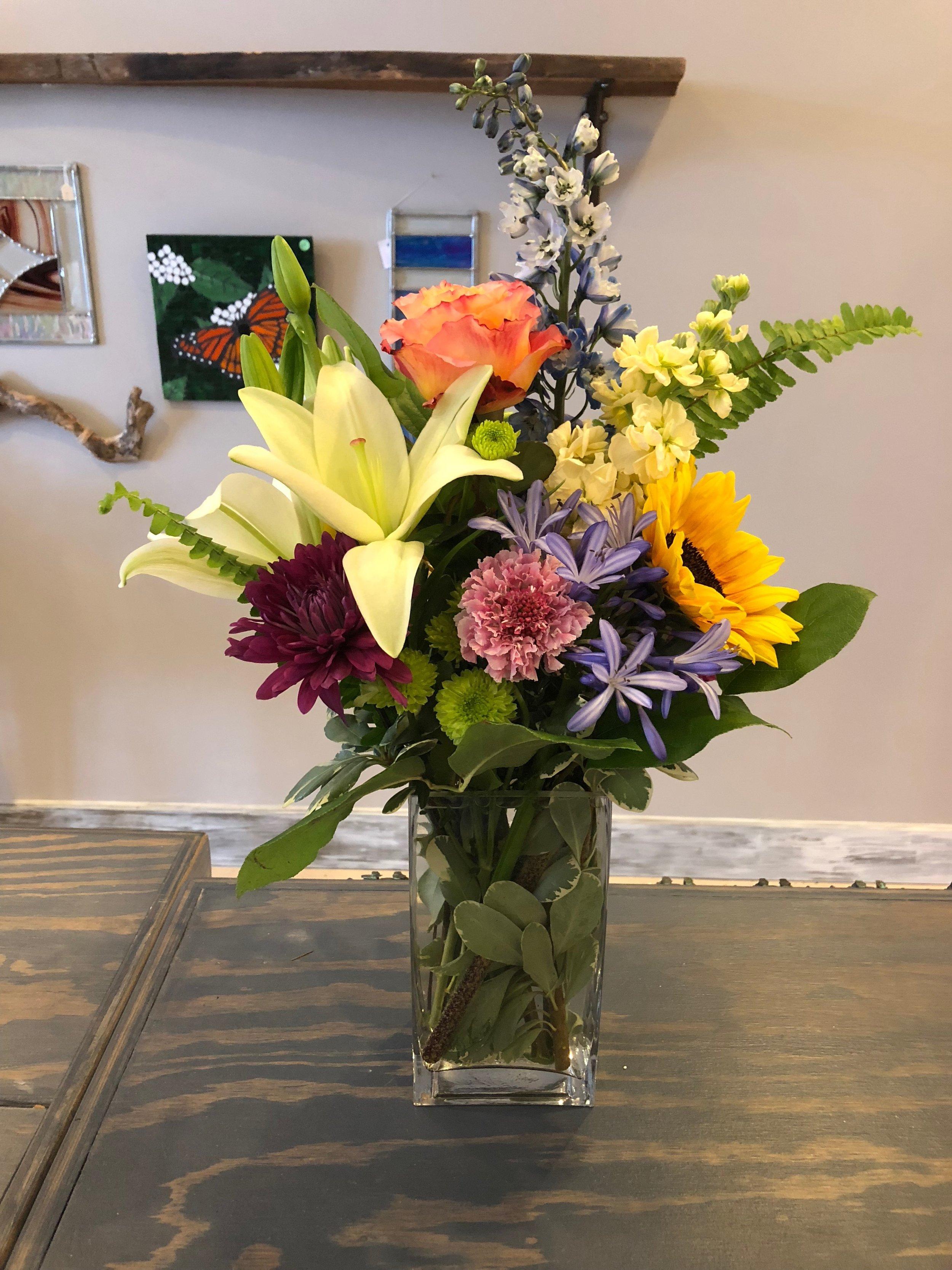 Deluxe - Seasonal mix of florals in an 8 inch vase.$50-75*Pictured arrangement $50