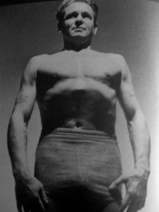 "Portrait of Joe Pilates with ""scooped"" abdomen where the transversus abdominus and obliques are activated, the abdomenal muscular corset compressed and lifted in and up."