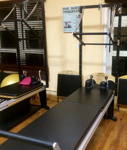 One of SOMA's Pilates Reformers converted into a Tower Unit. The Tower unit plus the elevated mat below it approximate half a Trapeze table. The Tower unit has a push through bar just like the Trapeze Table and additional springs can be attached for arms and legs. However, as the Tower Unit does not have overhead, horizontal bars, it lacks the versatility to suspend the body as the Trapeze Table does.