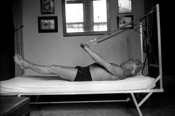 Joseph Pilates working out on his bednasium, the precursor to the Cadillac/Trapeze Table. The Cadillac evolved from the bednasium with the addition of taller posts and overhead, horizontal bars. The Trapeze table was nicknamed the Cadillac because of its versatility being used for everything from precision rehabilitation to high level athletic training.