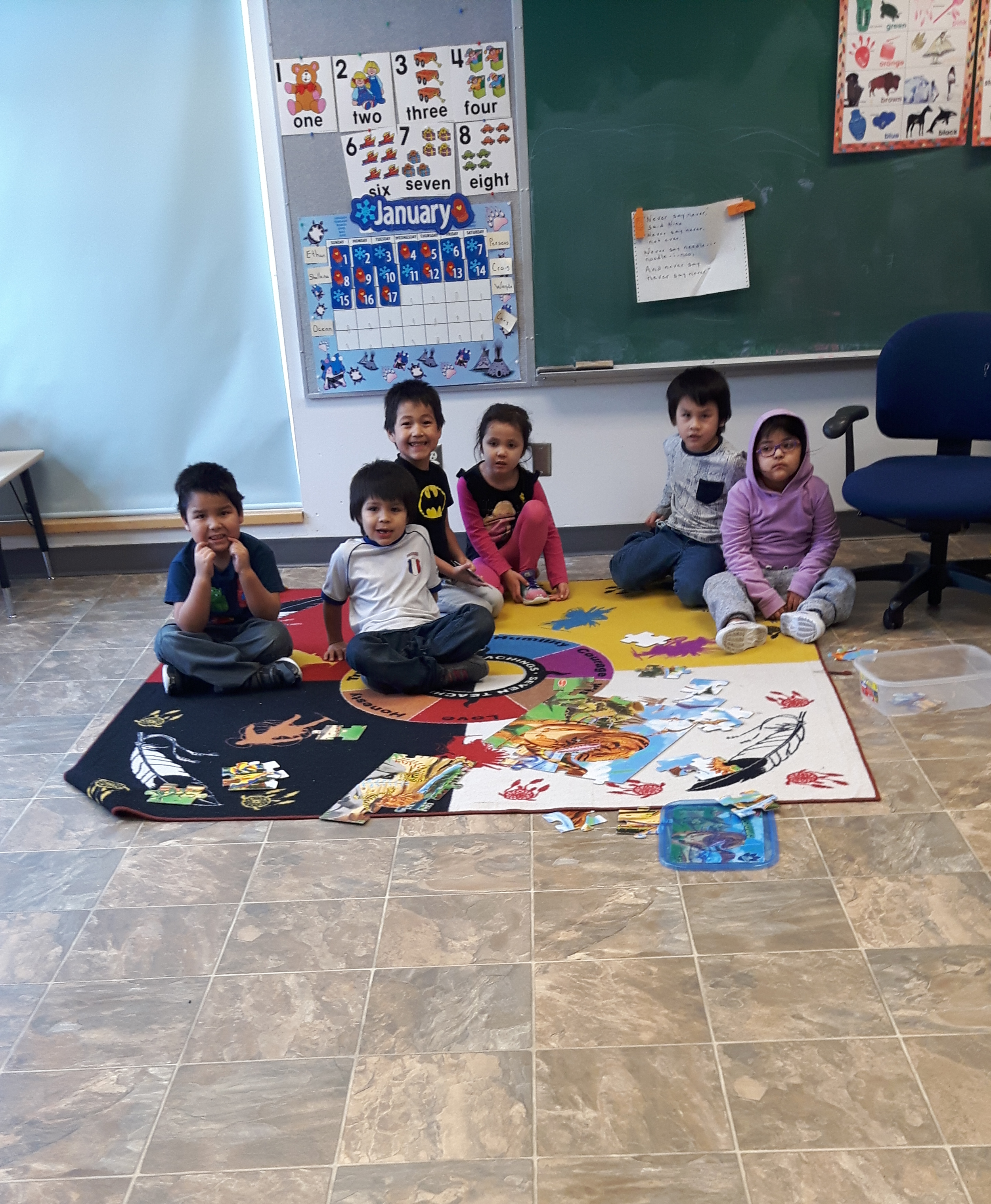 Students are in session working ona puzzle in the Nursery classroom, on the new floor.