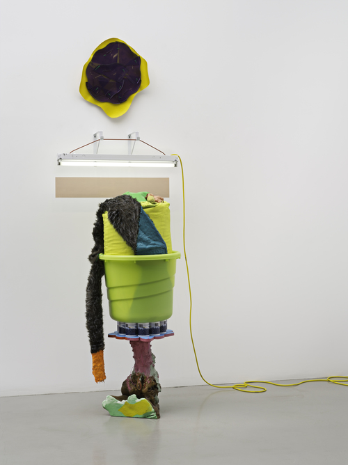 Untitled , 2009 vinyl, fluorescent fixture, electric cord, cable, hardware, yellow plastic tub, yellow laundry bag, Styrofoam stuffing, artifical lemons, acrylic and oil paint, coffee mugs with custom image, wooden base, ribbon, fake fur, plastic parts 109 x 37 x 40 in; 276.9 x 94 x 101.6 cm   Image courtesy Mitchell-Innes & Nash, New York  © Jessica Stockholder