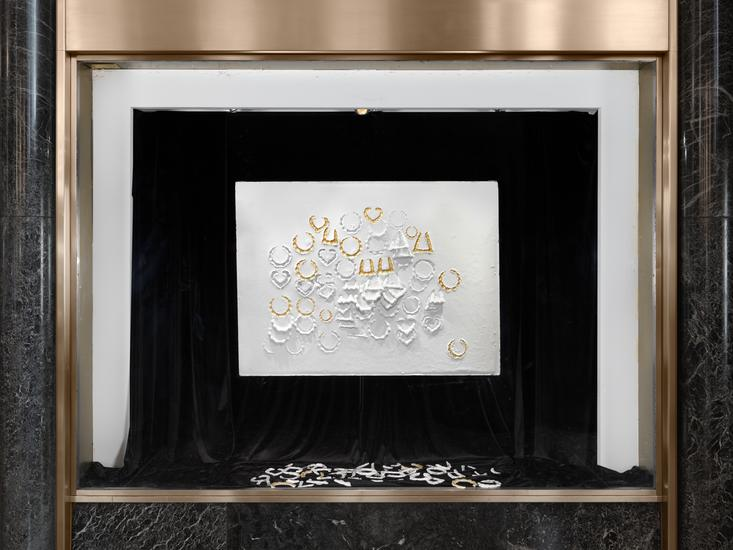 Install shot of LaKela Brown,  Horizontal Composition with Embedded and Impressed Doorknocker Earrings with Gold ( 2019) Plaster, foam and acrylic, 33 x 45 x 3 inches. Located in the lobby of 45 Rockefeller Plaza. Photo by Dan Bradica, courtesy of Art Production Fund.