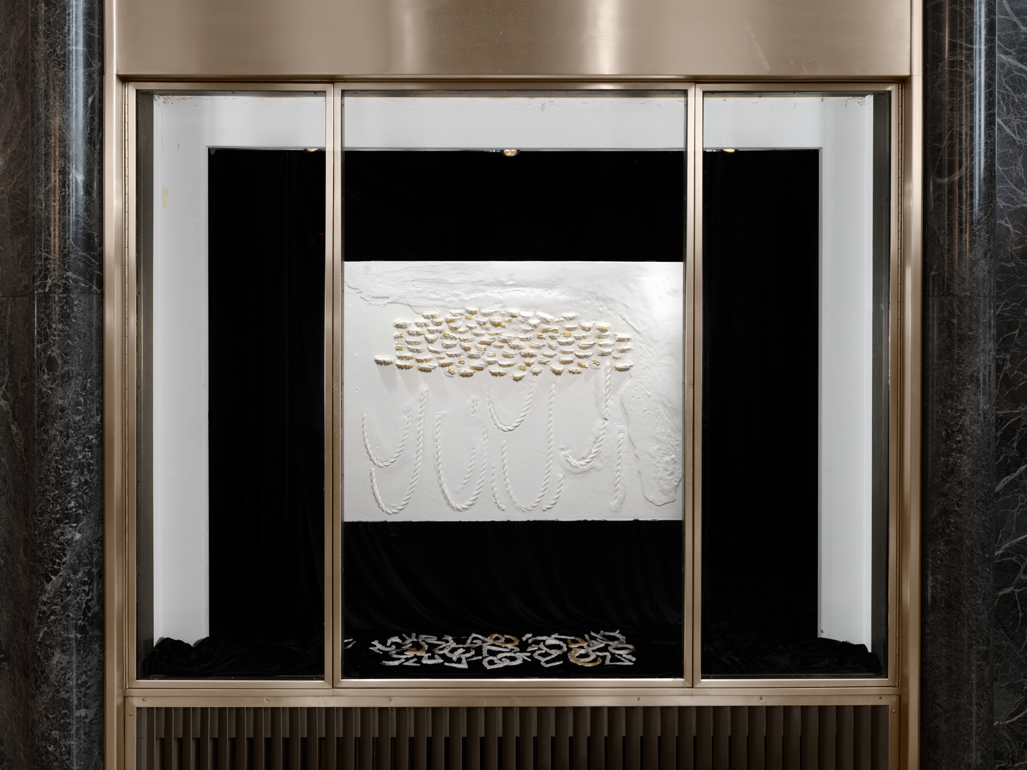 Install shot of LaKela Brown,  Horizontal Composition with Gold Teeth and Ropes #1  (2019) Plaster, foam and acrylic,. 33 x 45 inches. Located in the lobby of 45 Rockefeller Plaza. Photo by Dan Bradica, courtesy of Art Production Fund.