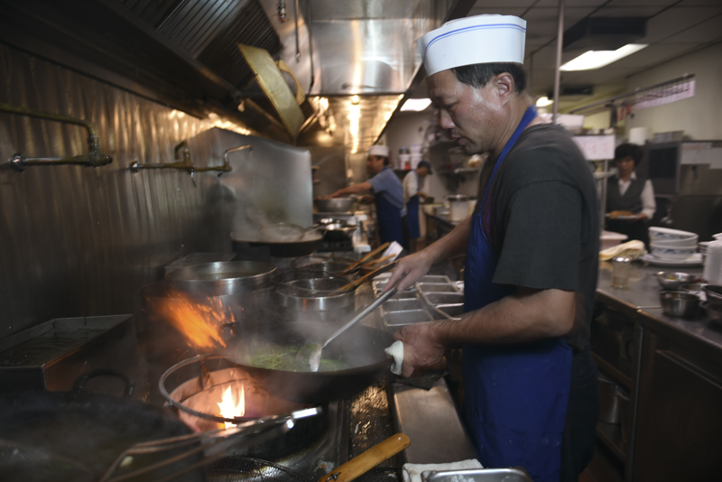 Zeng Yong stir frys a vegetable dish at the Diamond Palace Chinese Restaurant in Diamond Bar, Calif. Yong uses a traditional wok hei method of cooking, which is when a dish is cooked in a seasoned wok over an open flame and quickly tossed.
