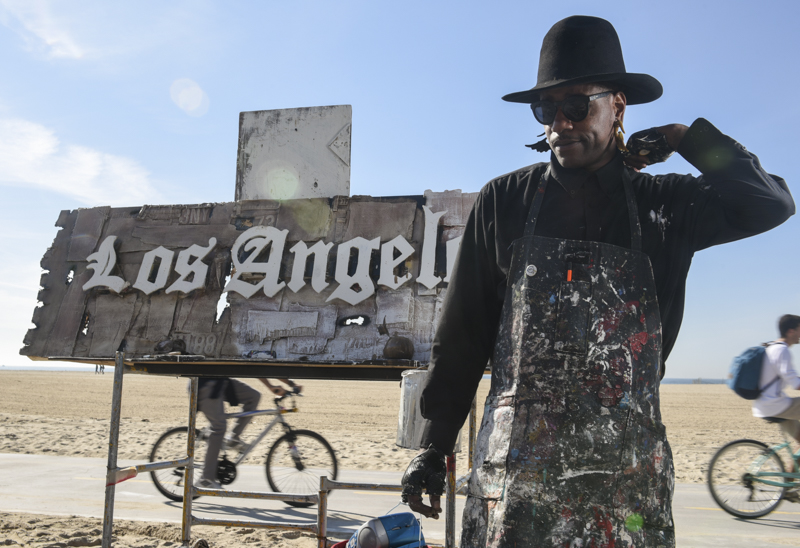 """Flewnt holds a blunt while displaying his assemblage-style artwork on the Boardwalk in Venice Beach, Calif. Although he may not always use it for its medicinal benefits, Flewnt smokes marijuana to help ease his chronic back pain and anxiety. Laws in California state that you can't smoke marijuana in public, but police officers don't necessarily enforce the rules of it in this area of the city. """"I put it out out of respect,"""" Flewnt said while explaining what he does when law enforcement walks by."""