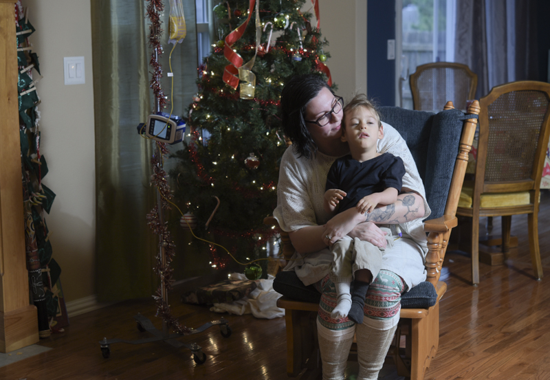 """Ashley Markum holds her youngest son Ayden Markum, 3, in their home in Rogersville, MO. At 18 months old, Ayden was diagnosed with cerebral palsy and infantile spasms. After multiple medications failed to treat his seizures, Ayden's parents began to look into alternatives , which led them to CDB oil. """"It has been the single most medicine that has helped,"""" Ashley said, """"After trying CBD for the first time...he laughed for the first time, and started to make eye contact; different developmental things along with seizure reduction."""" CBD oil is only available for patients who have specific siezure disorders and have a neurologist's recommendation. Although CDB oil does help Ayden reduce his seizures, it is not sufficient in subsiding the symptoms of his cerebral palsy. With THC, Ayden's muscle would be able to relax, but THC is not yet legally avilable for patients in Missouri. The Markums have previously debated on moving out of state to obtain the necessary medication for Ayden, but since CDB oil significantly helps with his Hypsarrhythmia, they decided to stay in Missouri and fight for the legalization of medical marijuana as a whole."""
